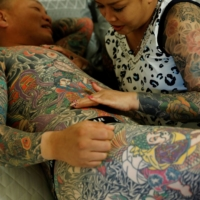 Bookkeeper Mina Yoshimura, 40, who works at her husband Hiroshi Yoshimura's company, touches a new tattoo that he got the same day, at their home in Tokyo on Oct. 2. | REUTERS
