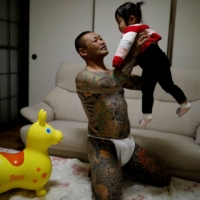 Scrap yard worker Hiroyuki Nemoto, 48, wears a traditional Japanese loincloth as he poses for a photo with his 1-year-old daughter, Tsumugi, at their house in Hitachinaka, Ibaraki Prefecture, in January. | REUTERS