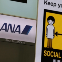 The logo of All Nippon Airways is seen on its counter in front of a social distancing sign at Haneda Airport in Tokyo on Tuesday. | REUTERS