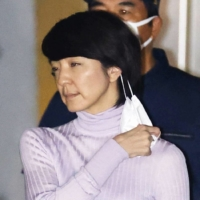 Anri Kawai takes off a face mask before bowing after she was released on bail from the Tokyo Detention House on Tuesday night. | KYODO