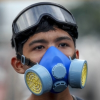A front-line pro-democracy student demonstrator in protective gear looks on during a rally in Bangkok earlier this month.  | AP