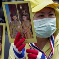 A supporter of the Thai monarchy displays images of King Maha Vajiralongkorn and Queen Suthida during a gathering outside the German Embassy in central Bangkok on Monday.  | AP