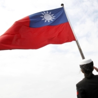 A Taiwanese military officer salutes toward Taiwan's flag onboard a navy frigate during military exercises off Kaohsiung, Taiwan, in January 2018. | AP