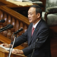 Prime Minister Yoshihide Suga responds to questions at the Lower House plenary session Wednesday. | KYODO