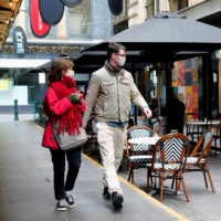 People walk past a cafe Wednesday after COVID-19 restrictions were eased in Melbourne | REUTERS