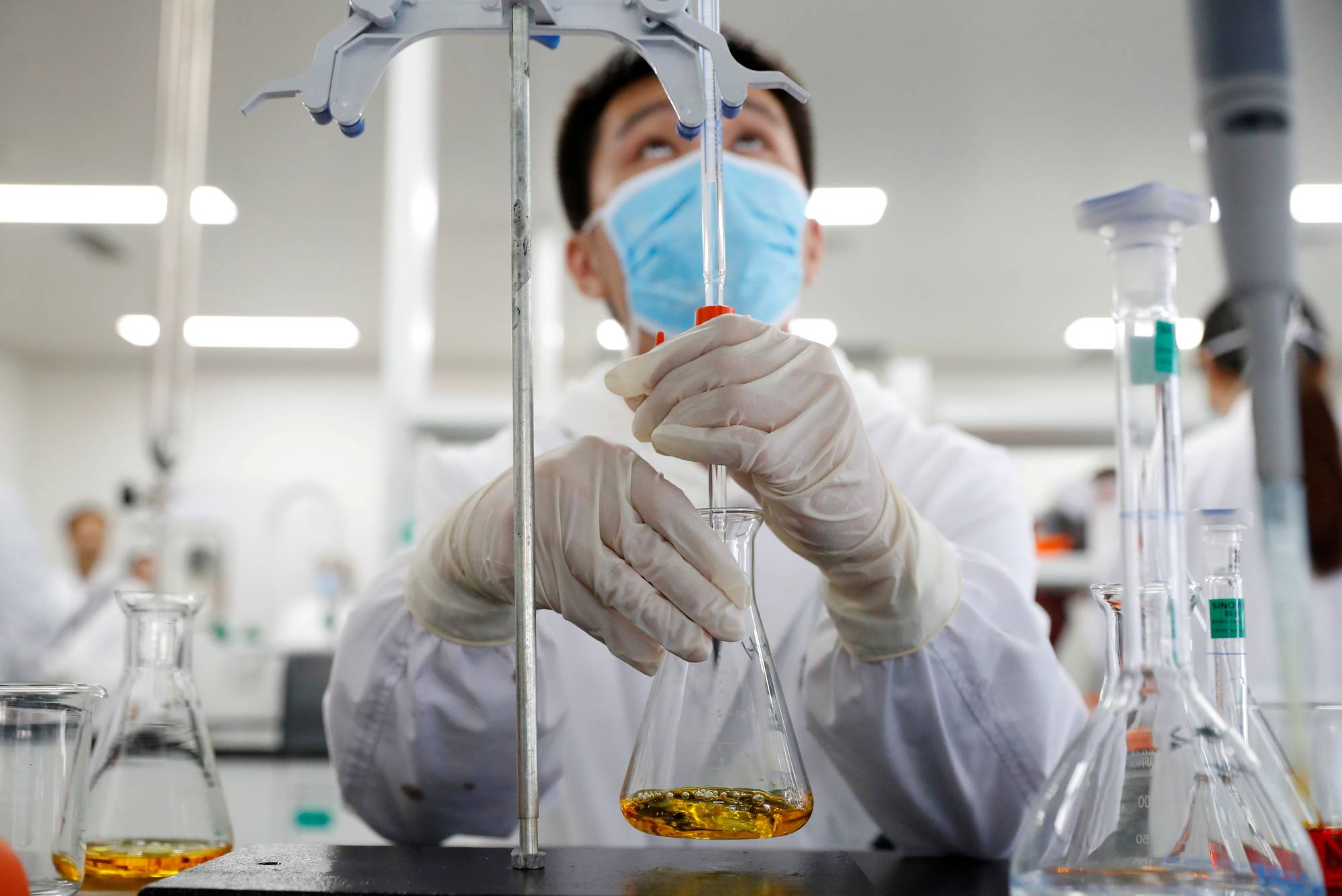 A man works in a laboratory in China that is developing an experimental COVID-19 vaccine. Three Chinese companies committed 250 million doses of vaccines to Indonesia. | REUTERS