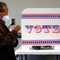 A woman casts her vote at a polling site in Milwaukee on Oct. 20.  | REUTERS