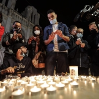 People lights candles outside the Notre-Dame de l'Assomption Basilica in Nice on Thursday in tribute to the three victims of a knife attacker inside a church in the city.  | AFP-JIJI