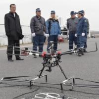 The National Police Agency conducts an anti-terrorism drill in Tokyo's Koto Ward in January 2016 using its interceptor drone (above) to catch another drone (below). | KYODO