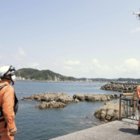 Firefighters fly a drone over waters in Hayama, Kanagawa Prefecture, in August as part of a rescue drill as no lifeguards were deployed during the swimming season amid the COVID-19 pandemic. | KYODO