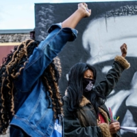 Paris Stevens (left) and Angela Harrelson, George Floyd's cousin and aunt, respectively, hold their fists as people gather in celebration of what would have been his 47th birthday, on Oct. 14.  | AFP-JIJI
