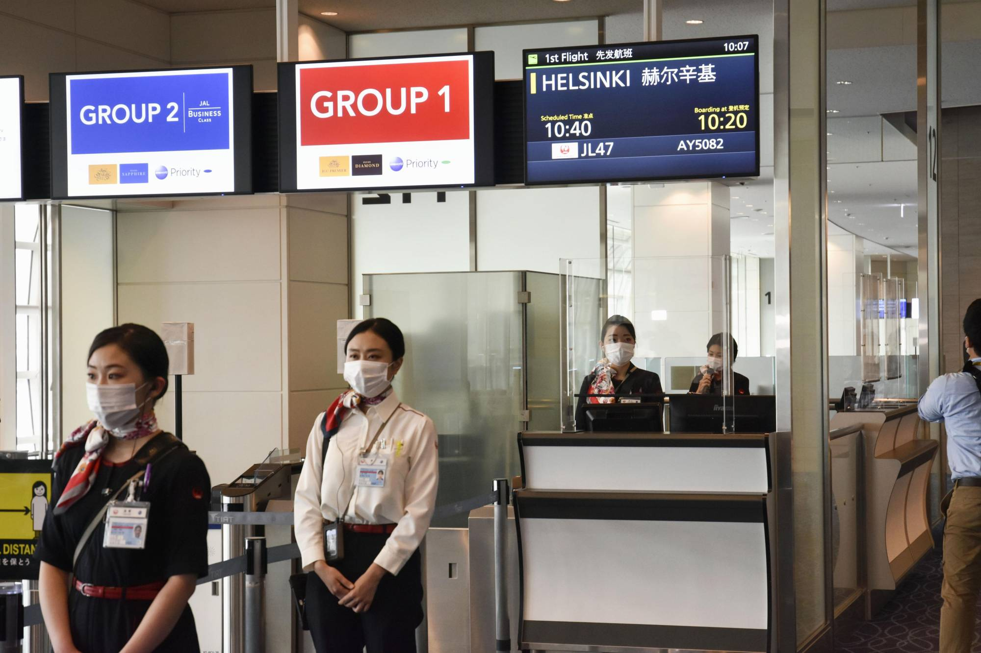 Airline staff are seen at a boarding gate for international flights at Haneda Airport earlier this month. | KYODO