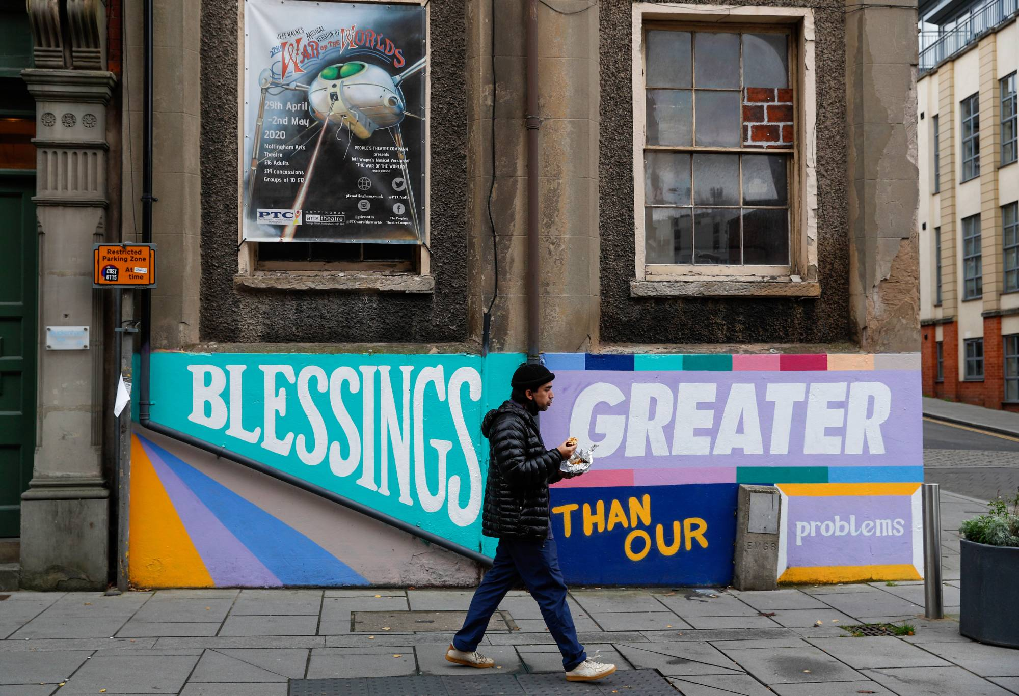 A pedestrian walks past the Arts Theatre in Nottingham, England, as the city headed into the highest level of coronavirus restrictions on Friday. | BLOOMBERG
