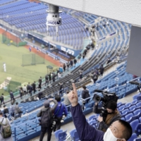 An official points to an anemometer installed at Yokohama Stadium as part of a high-tech experiment to mitigate the spread of the novel coronavirus at major events. | KYODO
