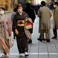 Women wearing kimono and masks walk in Tokyo on Nov. 13 | REUTERS