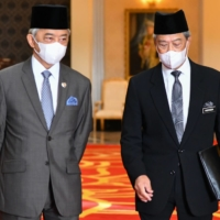 This handout picture taken and released by Malaysia's National Palace on October 28, 2020 shows Malaysian Prime Minister Muhyiddin Yassin (right) meets with Malaysian King Sultan Abdullah Sultan Ahmad Shah at the National Palace in Kuala Lumpur on Wednesday.  | MALAYSIA NATIONAL PALACE / VIA AFP-JIJI