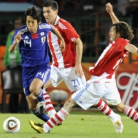 Kengo Nakamura (left) dribbles the ball past a Paraguay defender during a FIFA World Cup round-of-16 match on June 29, 2010, in Pretoria, South Africa. | KYODO