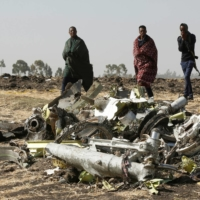Ethiopian police officers walk past the debris of the Ethiopian Airlines Flight ET 302 plane crash, near Addis Ababa on March 12, 2019.  | REUTERS