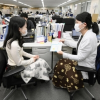 Staff at the Environment Ministry use blankets as the annual 'Warm Biz' energy-saving campaign kicked off Monday. | KYODO