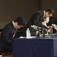 Ichiro Matsui (center), Osaka Mayor, and Hirofumi Yoshimura (left), Osaka Governor, apologize for losing the referendum at a news conference in Osaka on Sunday. | KYODO