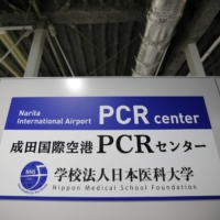 A sign board is displayed at the newly opened Narita International Airport PCR Center operated by Nippon Medical School Foundation. | REUTERS