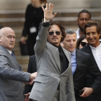 American actor Johnny Depp waves as he leaves after the end of the trial on July 28 at the High Court in London. The U.K. High Court has ruled against Johnny Depp in his libel suit against owner of Sun tabloid over wife-beating allegation, it was reported on Monday. | AP