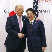 U.S. President Donald Trump shakes hands with Prime Minister Shinzo Abe at the Group of 20 (G-20) summit in Osaka in June 2019. | POOL / VIA BLOOMBERG