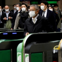 Passengers wear protective face masks at a Tokyo station in April after the government announced a state of emergency for the capital following the spread of COVID-19 to Japan. | REUTERS