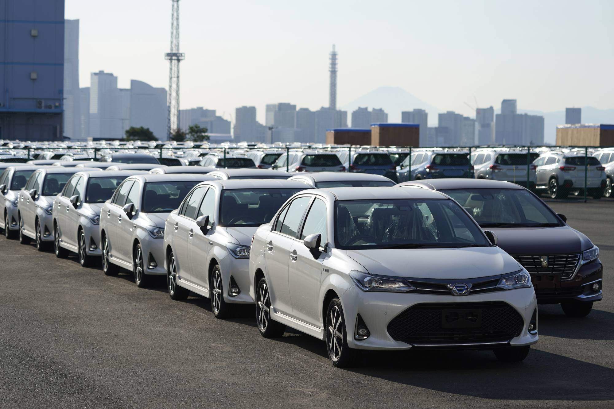 Toyota Motor Corp. vehicles bound for shipment are lined up at a port in Yokohama on Saturday. | BLOOMBERG