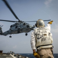 A sailor sends off an MH-60R Sea Hawk helicopter from the Royal Australian Navy frigate HMAS Ballarat as it takes off from the flight deck aboard the guided-missile destroyer USS John S. McCain. | U.S. NAVY