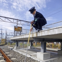 An official from East Japan Railway Co. picks up a wireless earphone from a railroad track using a grabber tool during a test conducted in Tokyo on Monday. | KYODO