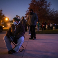 Jan Guess waits for the polls to open on Tuesday morning in Columbus, Ohio. | MADDIE MCGARVEY / THE NEW YORK TIMES