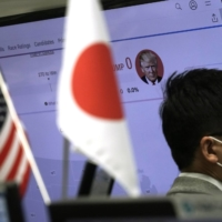 A money trader of a foreign exchange company works near a screen showing a news program on the U.S. elections on Wednesday in Tokyo. | AP