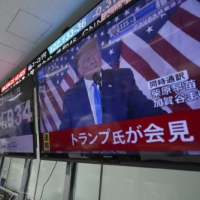 An employee at a foreign exchange trading company in Tokyo watches a broadcast of a news conference by U.S. President Donald Trump on Wednesday.  | AP