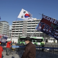 South Korean supporters of U.S. President Donald Trump hold flags near the U.S. Embassy in Seoul on Wednesday.  | AP
