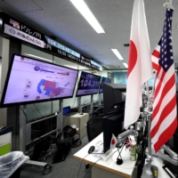 Foreign exchange traders work as a TV screen shows news updates on the U.S. presidential election in Tokyo on Thursday. | AFP-JIJI