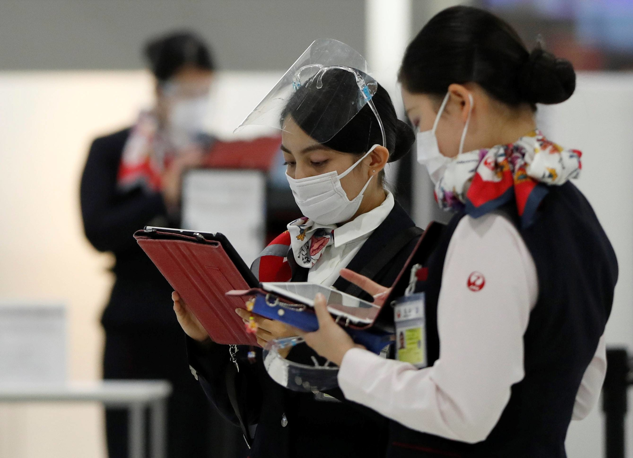 Japan Airlines employees at the departure area in Narita International Airport in Chiba Prefecture | REUTERS