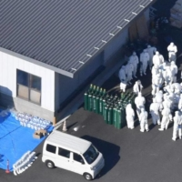 Workers in protective suits gather at a chicken farm in the city of Mitoyo, Kagawa Prefecture, on Thursday after an outbreak of highly pathogenic bird flu was confirmed there. | KYODO