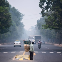 A vendor selling traditional snacks crosses a street amid smoggy conditions in New Delhi on Wednesday.  | AFP-JIJI