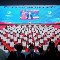 China's President Xi Jinping is seen on a screen in the media center as he speaks at the opening ceremony of the third China International Import Expo  in Shanghai on Wednesday. | REUTERS
