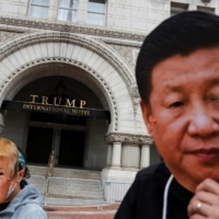 Protesters wear a face masks of China's President Xi Jinping and U.S. President Donald Trump during a demonstration in front of the Trump International Hotel in Washington, D.C. on October. | REUTERS