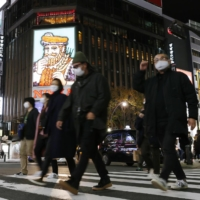People walk in the Susukino nightlife entertainment district of Sapporo in Hokkaido on Thursday. Some clusters of COVID-19 infections were reported there this week. | KYODO