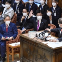 Chief Cabinet Secretary Katsuobu Kato raises his hand to answer a lawmaker's question in place of Prime Minister Yoshihide Suga in a meeting of the Lower House Budget Committee on Wednesday. | KYODO