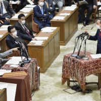 Prime Minister Yoshihide Suga answers questions from lawmaker Kiyomi Tsujimoto of the Constitutional Democratic Party of Japan during a meeting of the Lower House Budget Committee on Wednesday. | KYODO