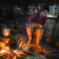 Naga tribesman Man Chen, 18, warms up in front of a fire in a house in his village in Lage, Myanmar.  | AFP-JIJI