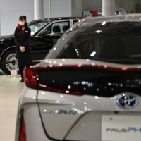 A staff member waits for customers at a Toyota Motor Corp. showroom in Tokyo. The firm almost doubled its full-year forecasts on Friday. | AFP-JIJI