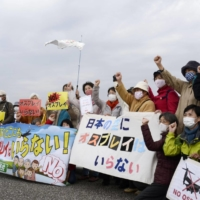 A group of local residents hold a rally Friday near Camp Kisarazu in Kisarazu, Chiba Prefecture, protesting against deployment of Ospreys the same day that the Ground Self-Defense Force started test flights. | KYODO