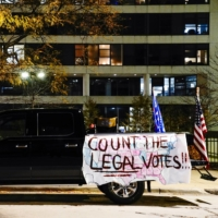 A banner reading 'Count the Legal Votes' and a U.S. and Trump flag hang from a pickup truck at a protest in Milwaukee, Wisconsin, on Thursday. | REUTERS