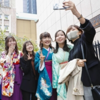 Graduates of Kyoritsu Women's University in Tokyo pose for a photograph at a graduation ceremony held on Tuesday. The ceremony was delayed due to the coronavirus. | KYODO