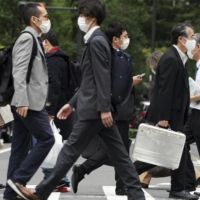 People walk Monday in Tokyo. Urban areas have been seeing high numbers of infections lately, with the nationwide daily figure at 1,141 on Friday, a day after the country's tally topped 1,000 for the first time since Aug. 21. | AP